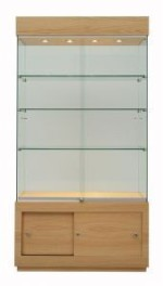 Tall glazed floor display cabinet with wooden base storage unit and wooden top with spotlights